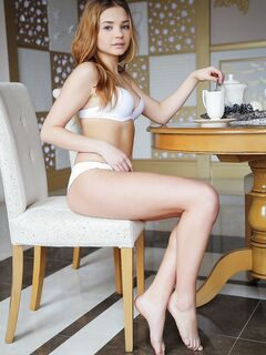 Молодая девушка сняла белое бельё за столом