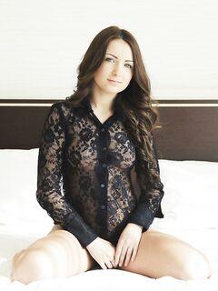 Сексуальная брюнетка широко раздвигает ноги в постели .