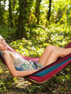 Голая девушка лежит в гамаке среди леса