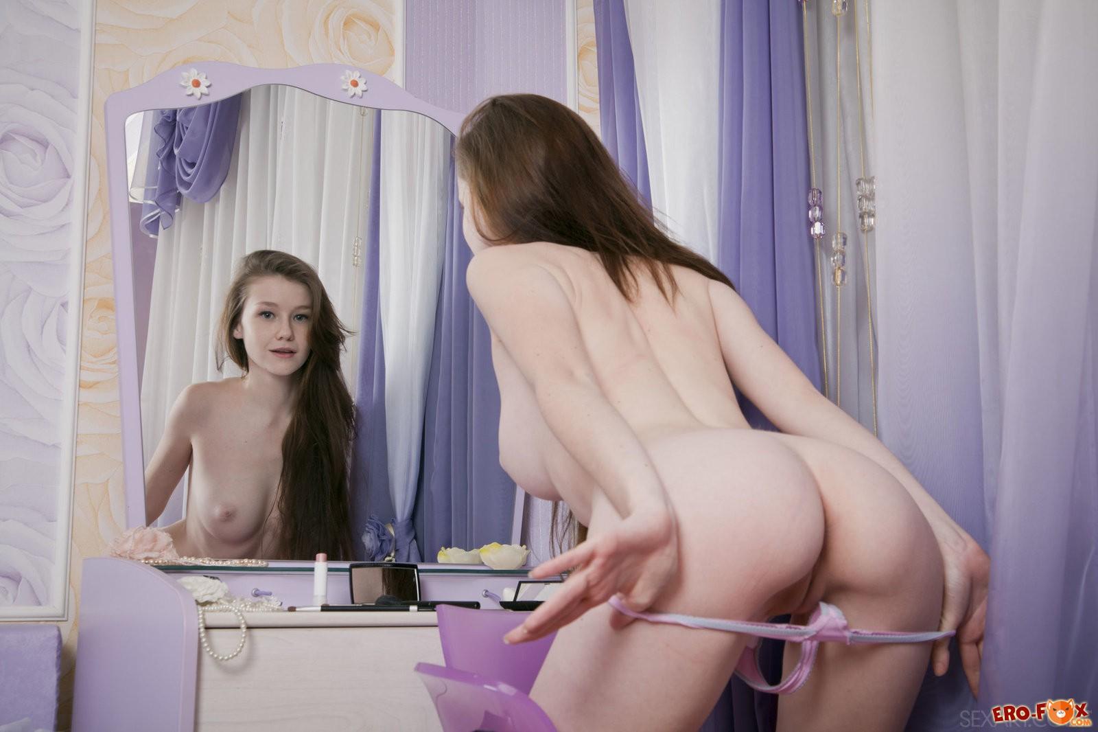 Молодая красивая девушка раздевается до гола в спальне
