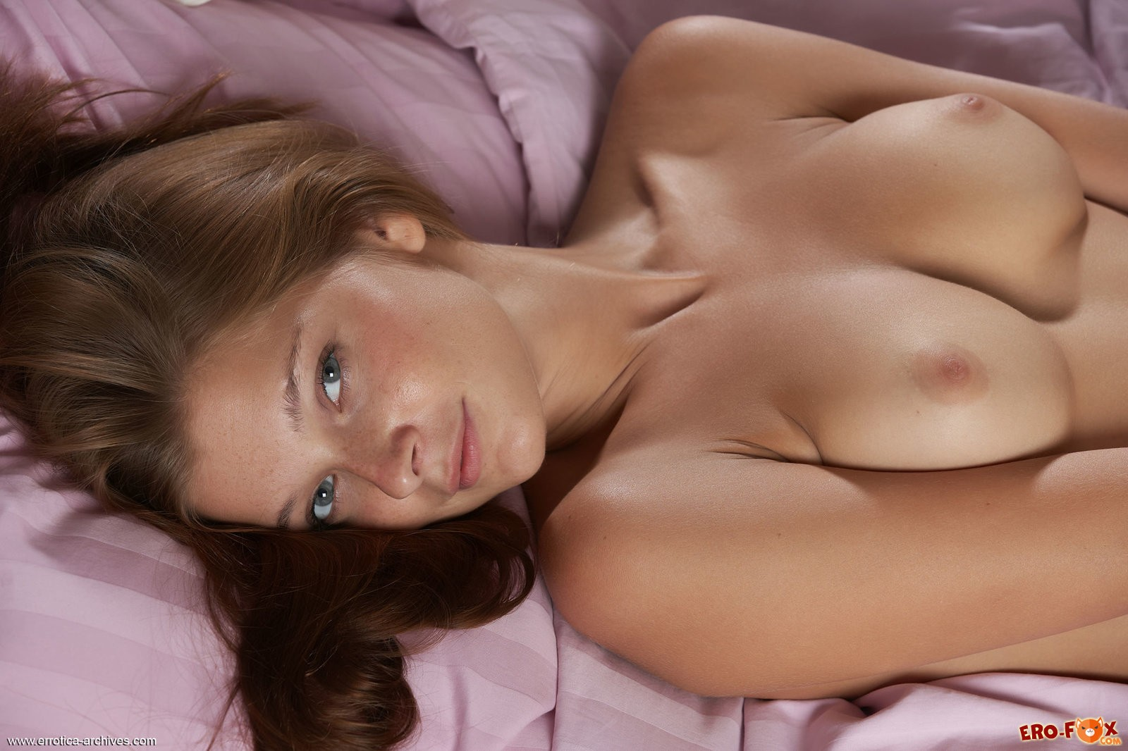 Голая девушка лежит в постели