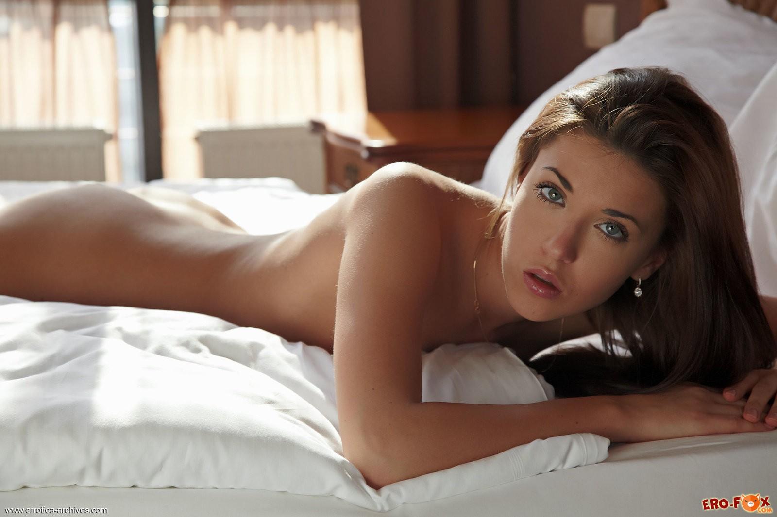 Красивая голая брюнетка в постели