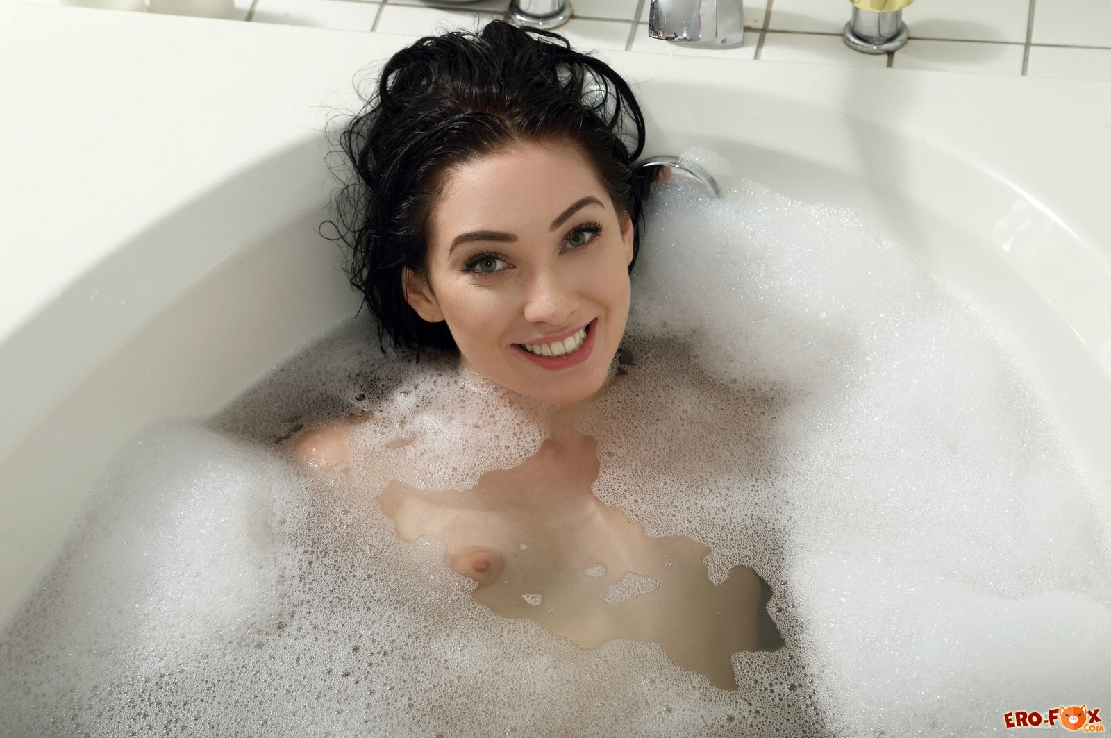 Голая попка девушки в ванной с пеной