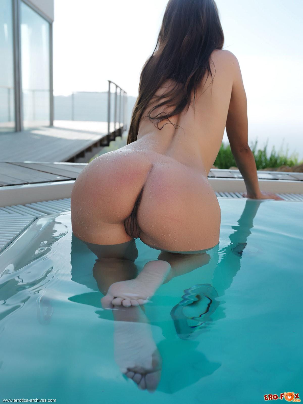 Голая девушка плавает в бассейне