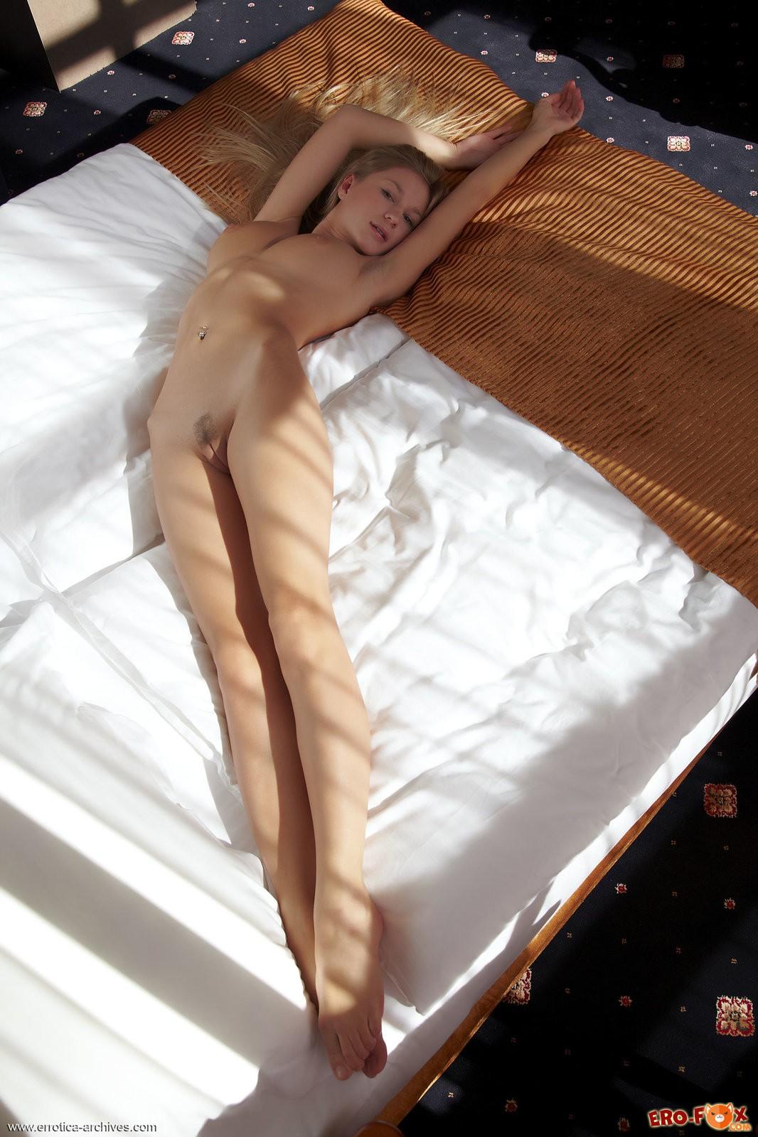 Голая блондинка нежится на кровати