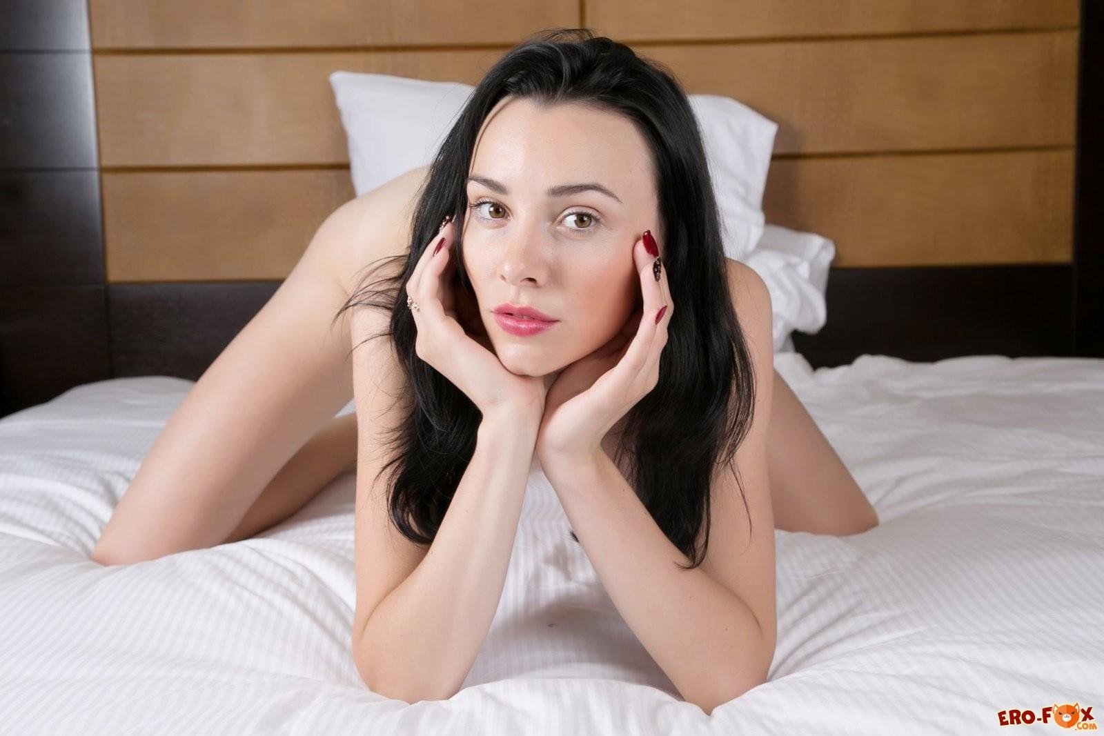 Гола брюнетка в постели с красной помадой