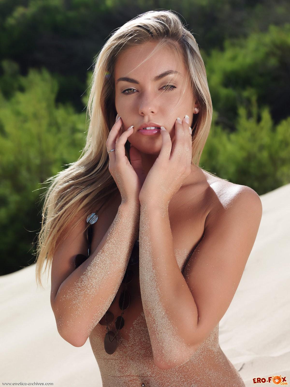 Голая блондинка на пляже в песке