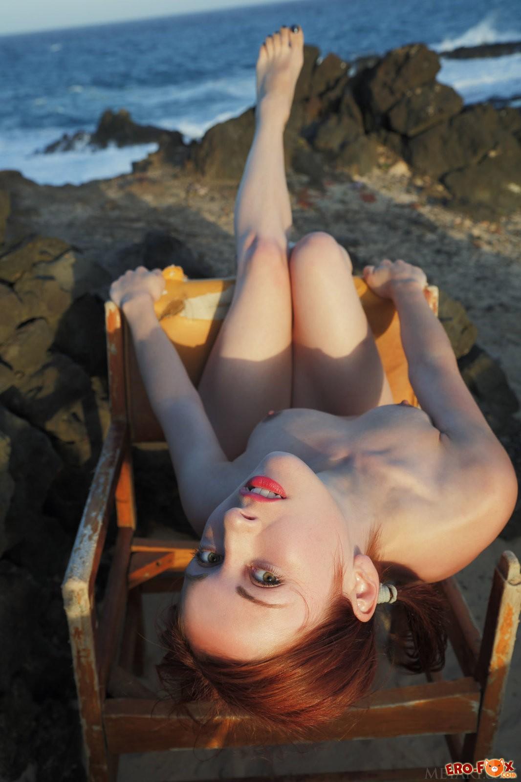 Рыжая девушка с маленькой грудью на берегу моря, фото голой.