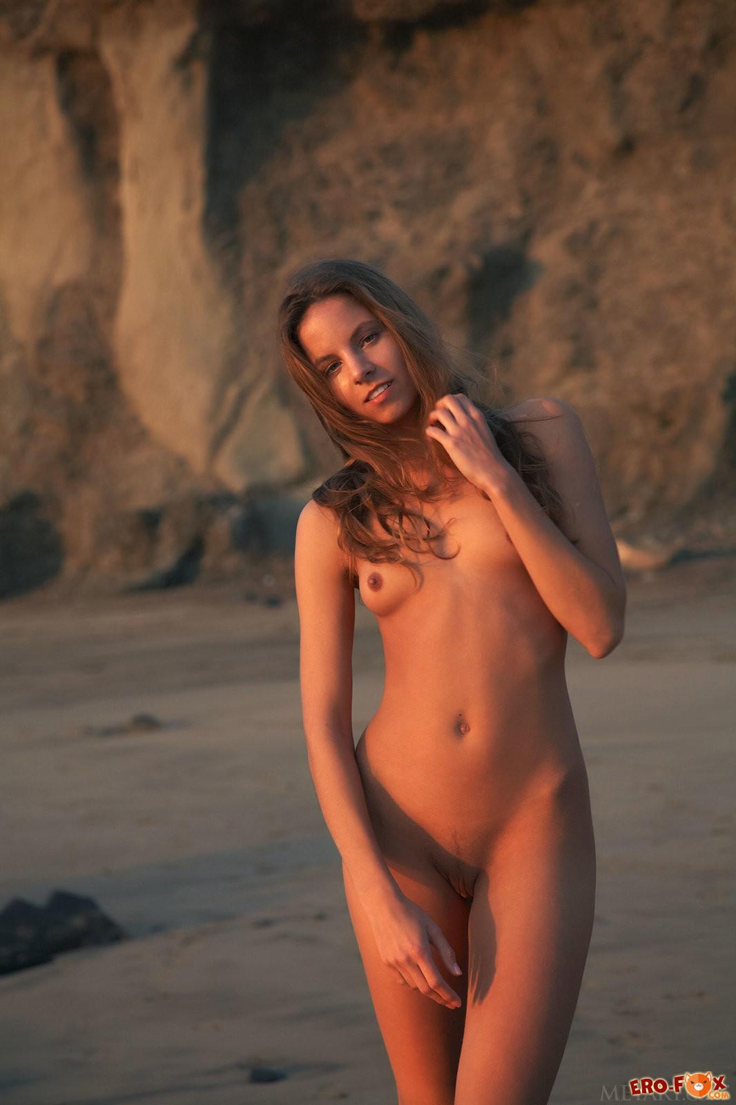Голая девушка с маленькой попкой на вечернем пляже .