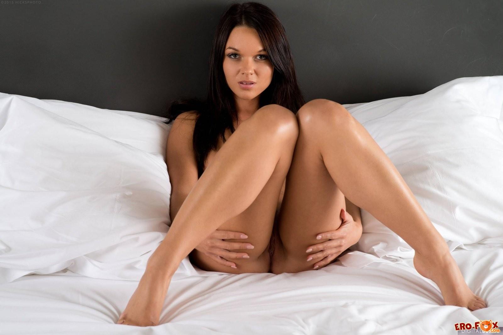 Обаятельная голая брюнетка в белой постели