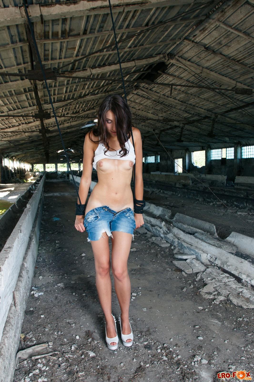 Тощая голая девушка в старом ангаре