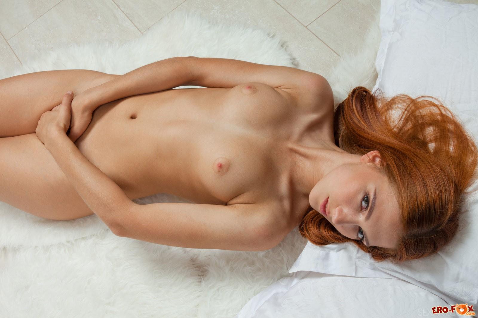 Голая рыжая девка попой к верху в постели,