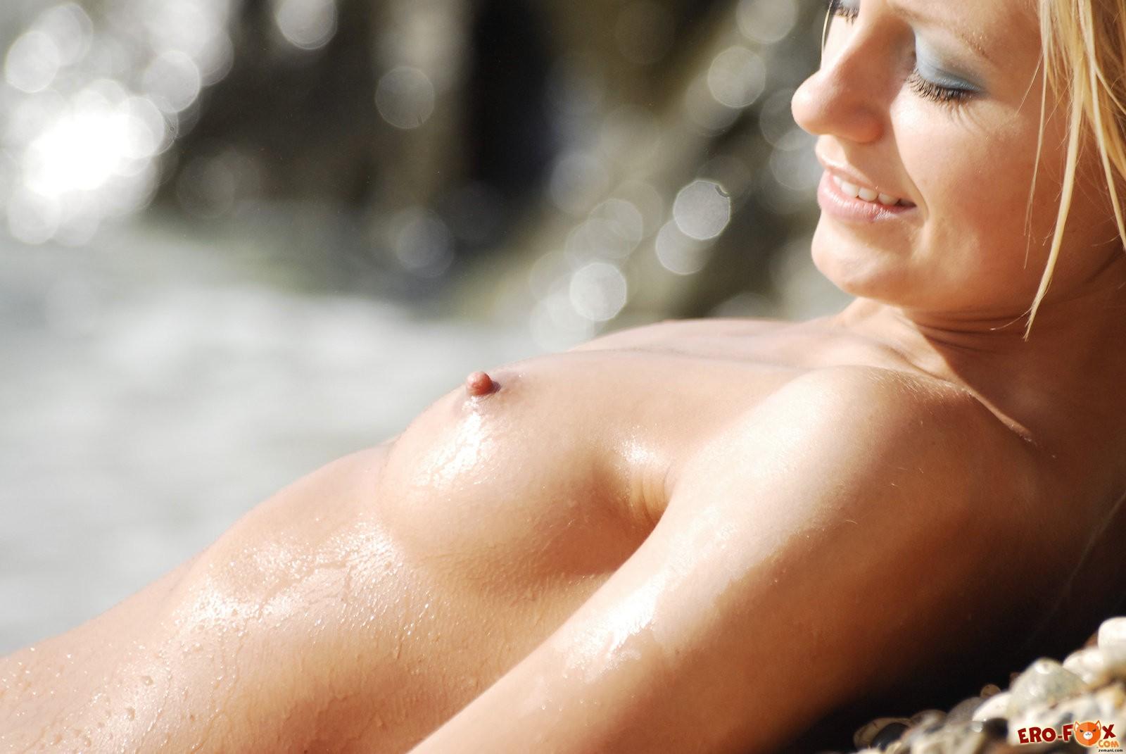 Голая блондинка на пляже купается