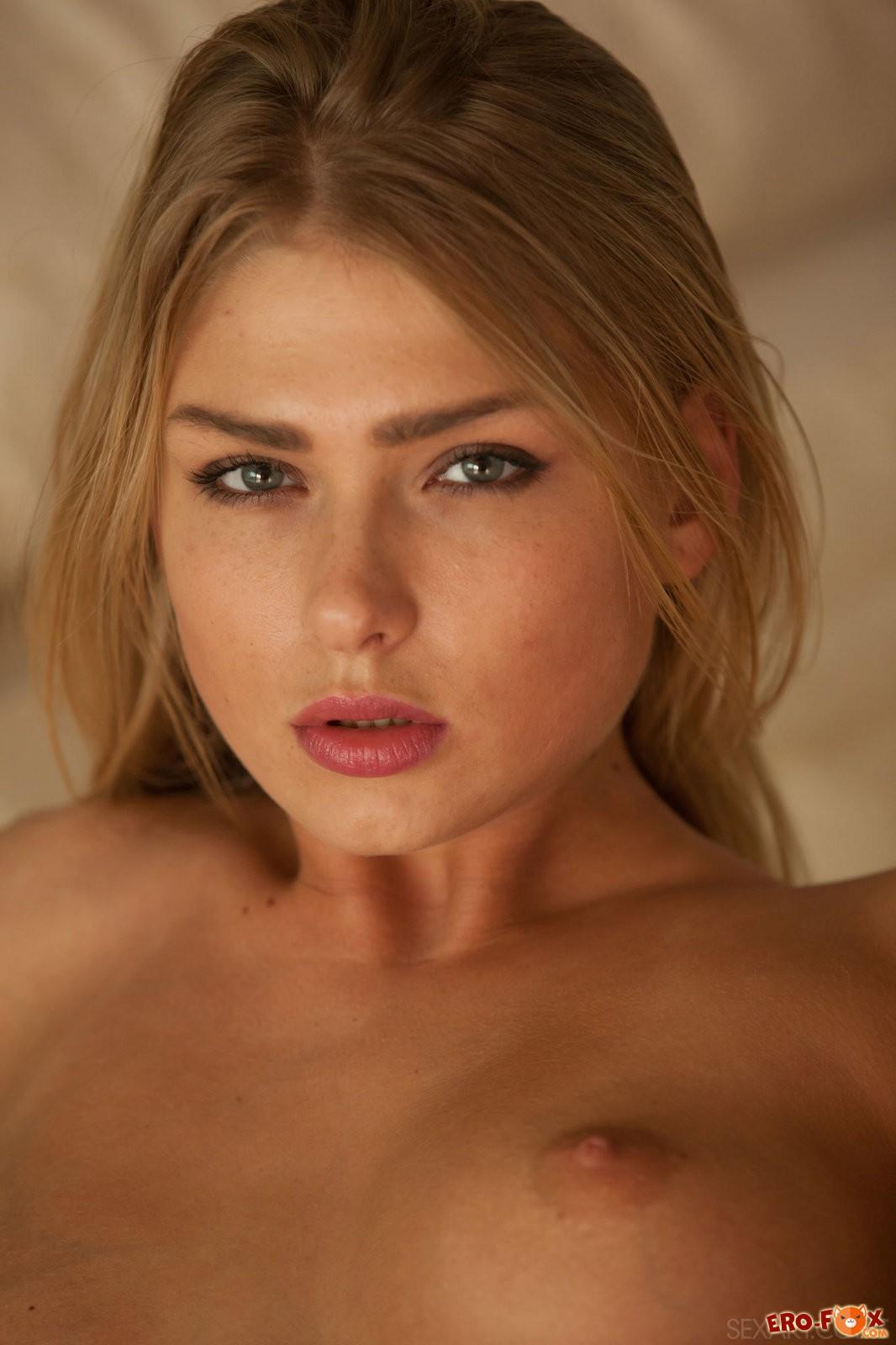 Блондинка в розовом белье раздевается в постели