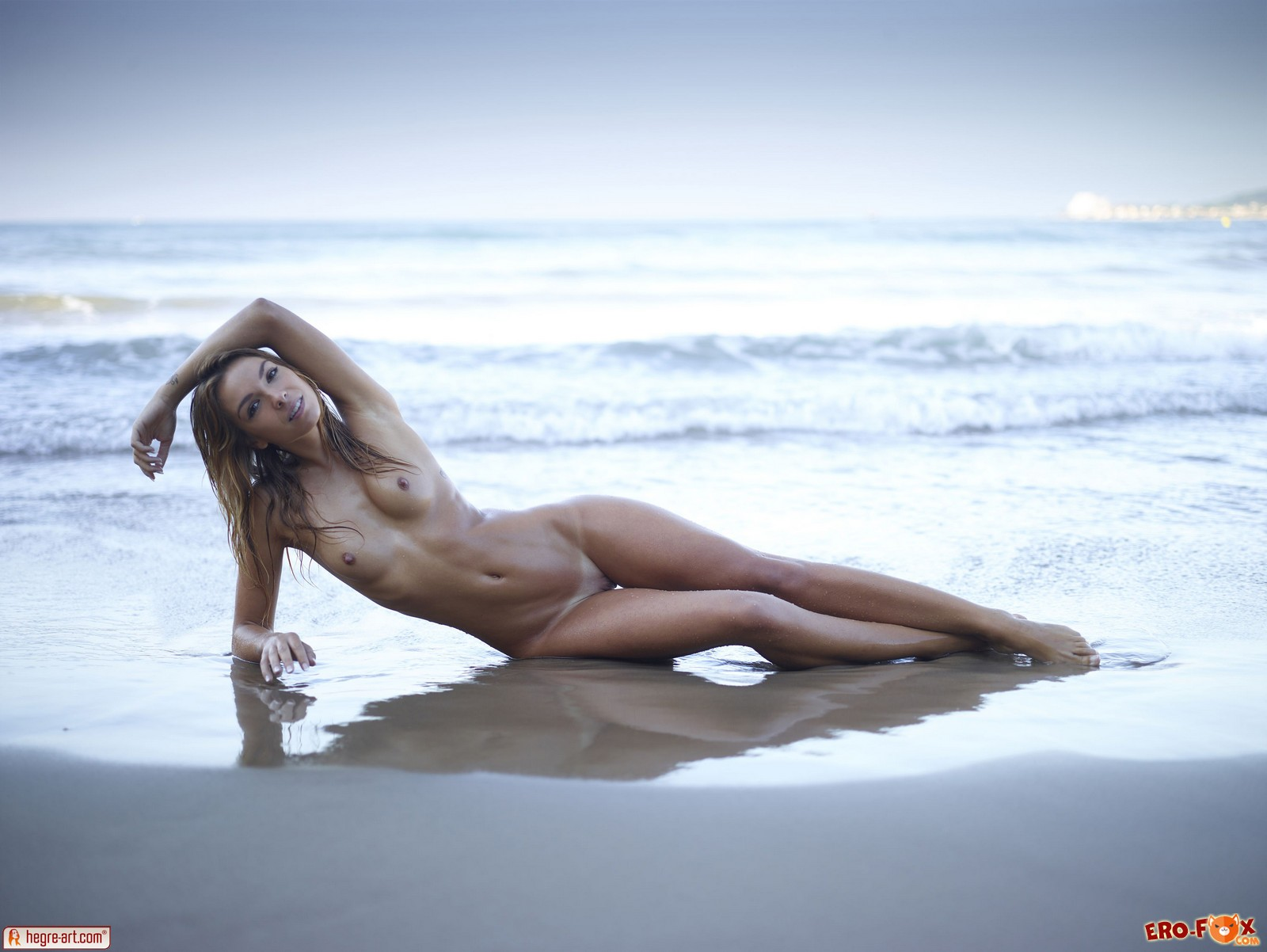 Худая голая девушка резвится на пляже