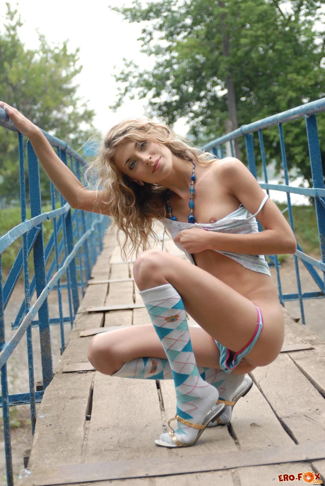 Девушка в майке и трусиках раздевается на мосту