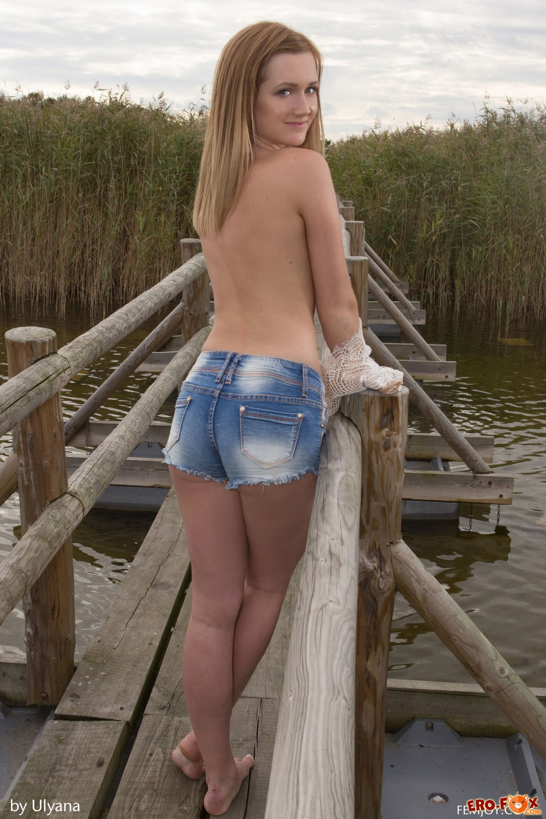Молодая голая девушка на старом мосту