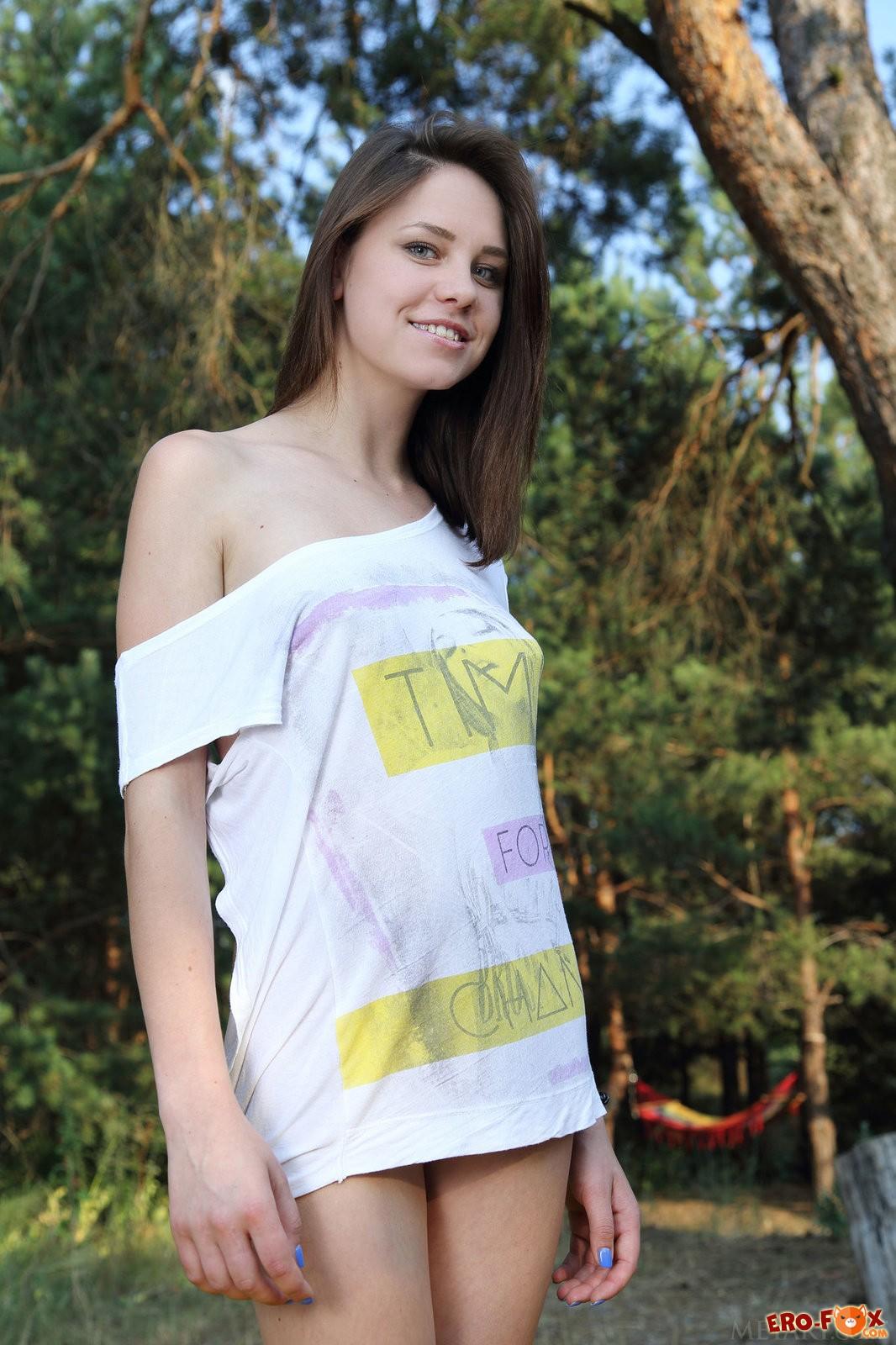 Молодая девушка голая позирует в лесу