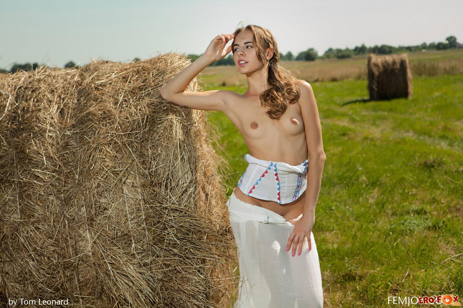 Деревенская голая девушка в поле у сена