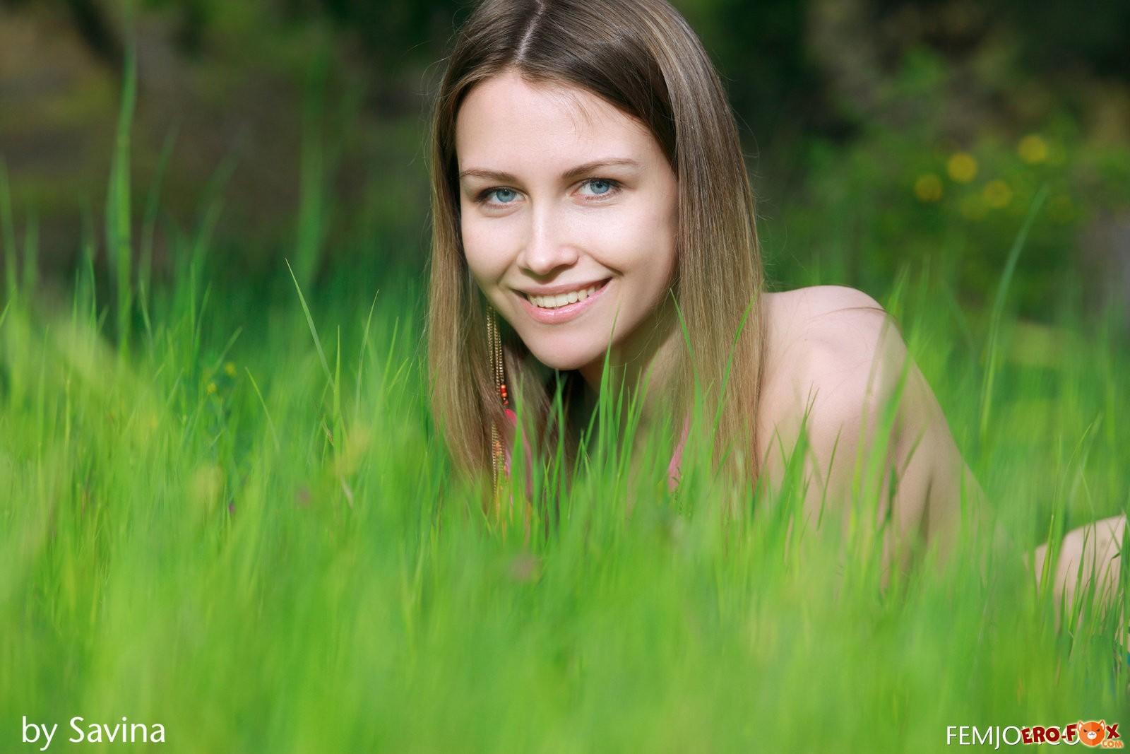 Красивая голая девушка в траве под ёлкой