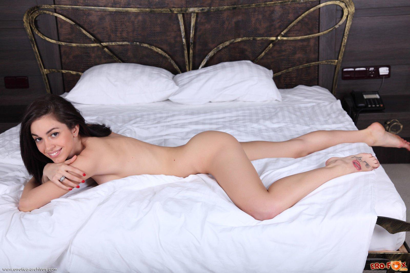 Голая брюнетка в постели своей спальни
