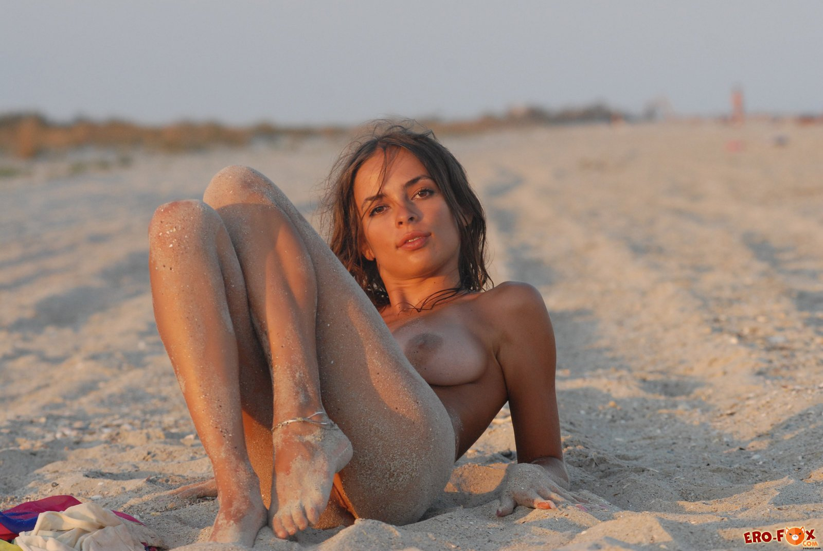 Грудастая голая девушка в песке на пляже