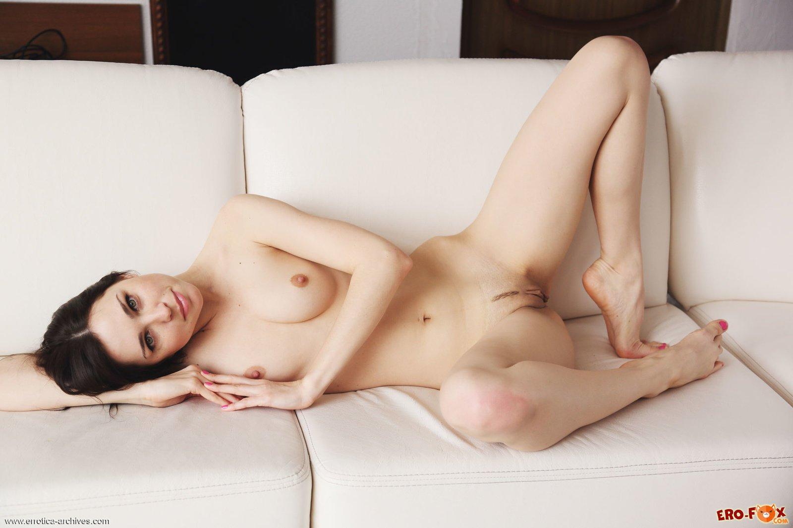 Голая брюнетка лежит на диване