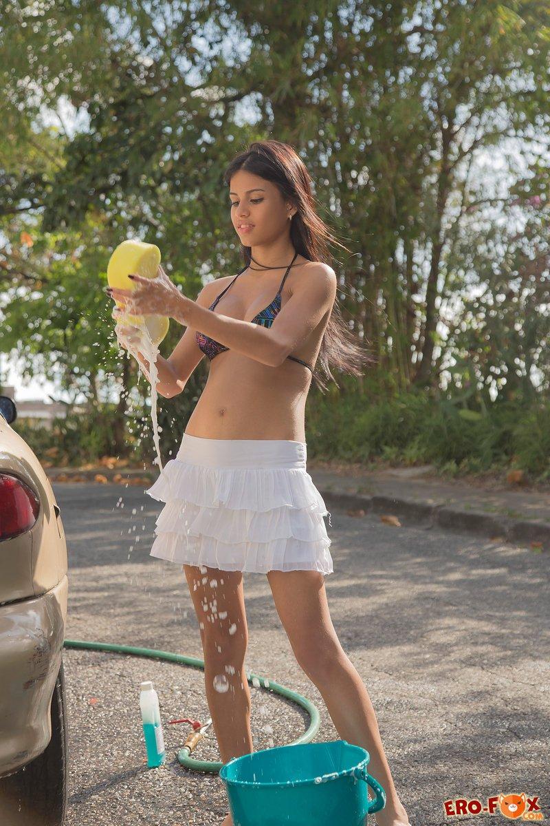 Девушка в купальнике моет машину с пеной