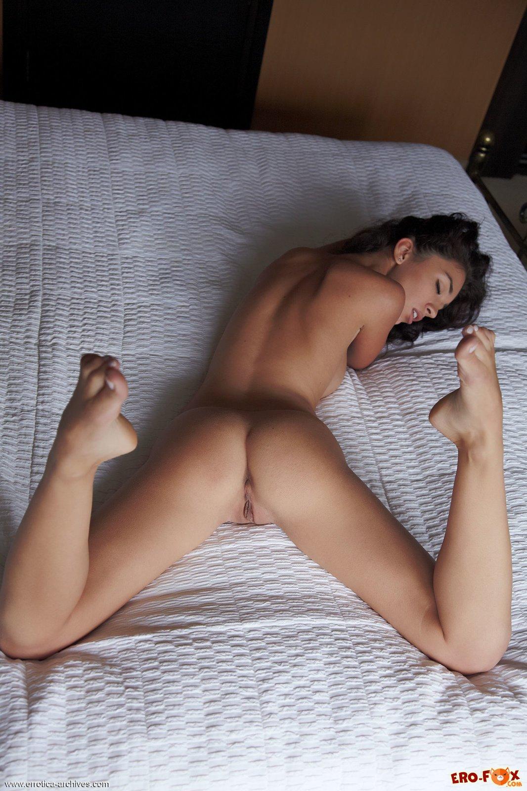 Сексуальная голая брюнетка в спальне на кровати .