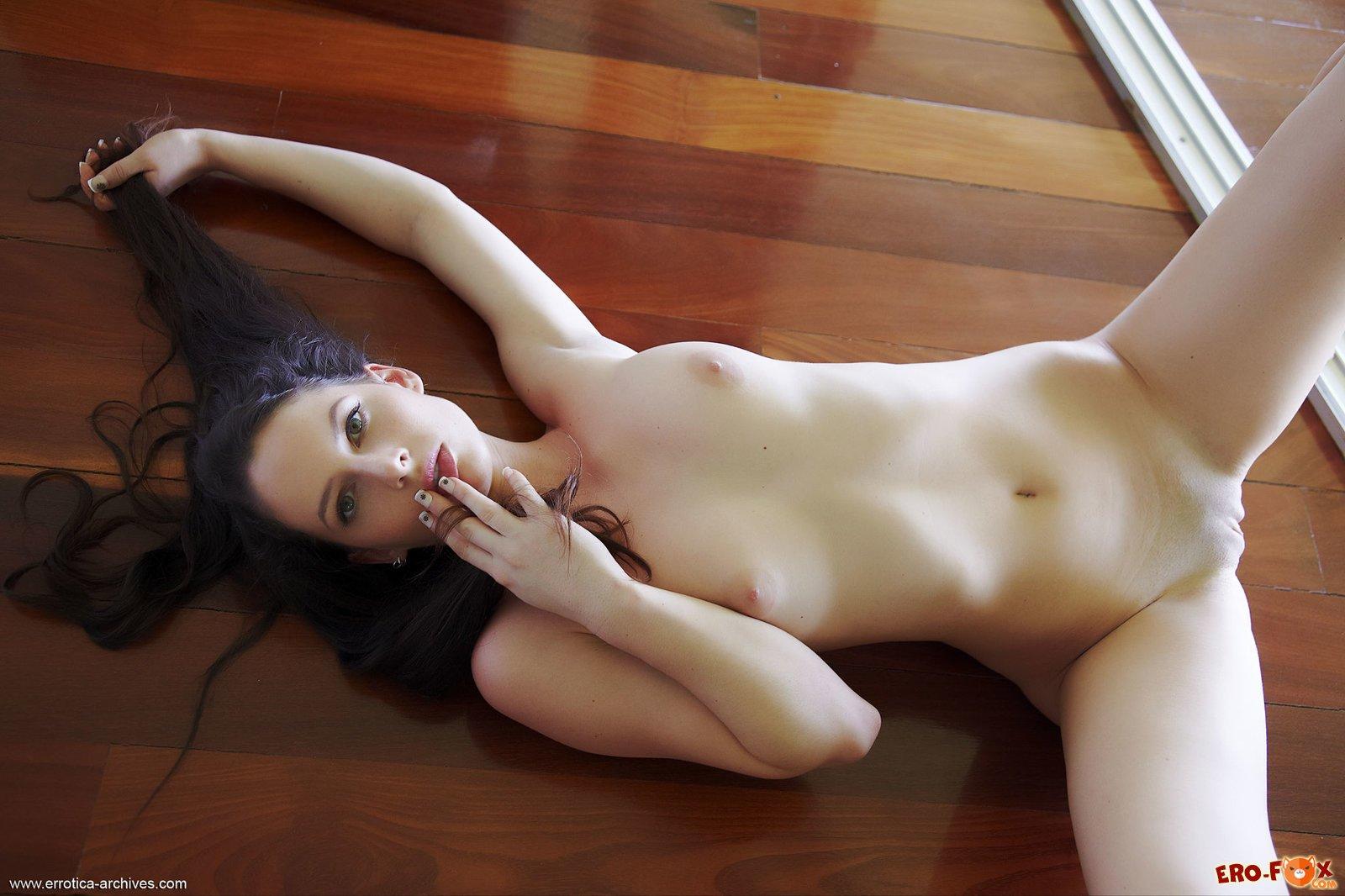 Голая брюнетка позирует на полу