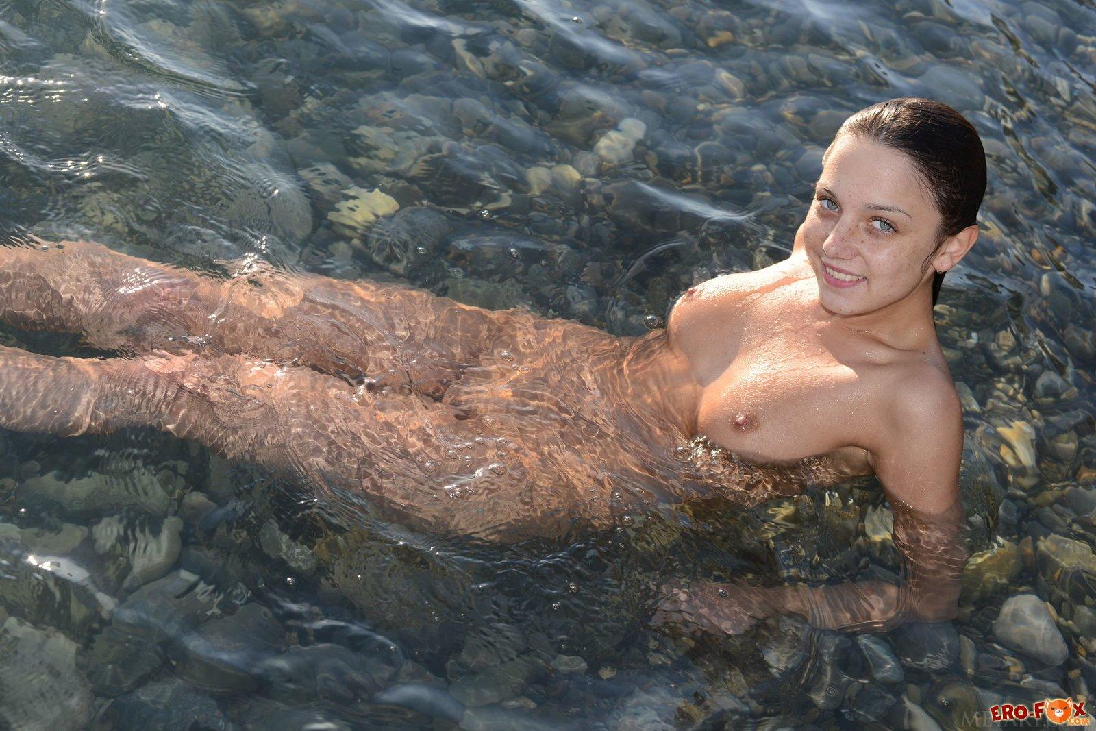 Голая девушка купается в море